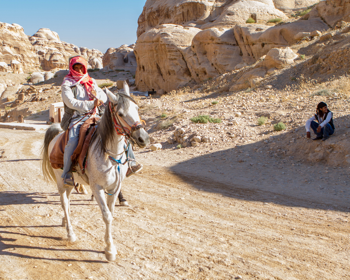 Petra for kids Bedouin horseman riding towards al Siq in Petra Jordan