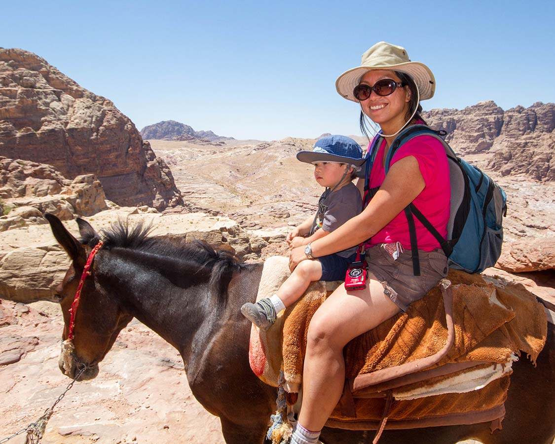 Christina Wagar rides a donkey in Petra with her son