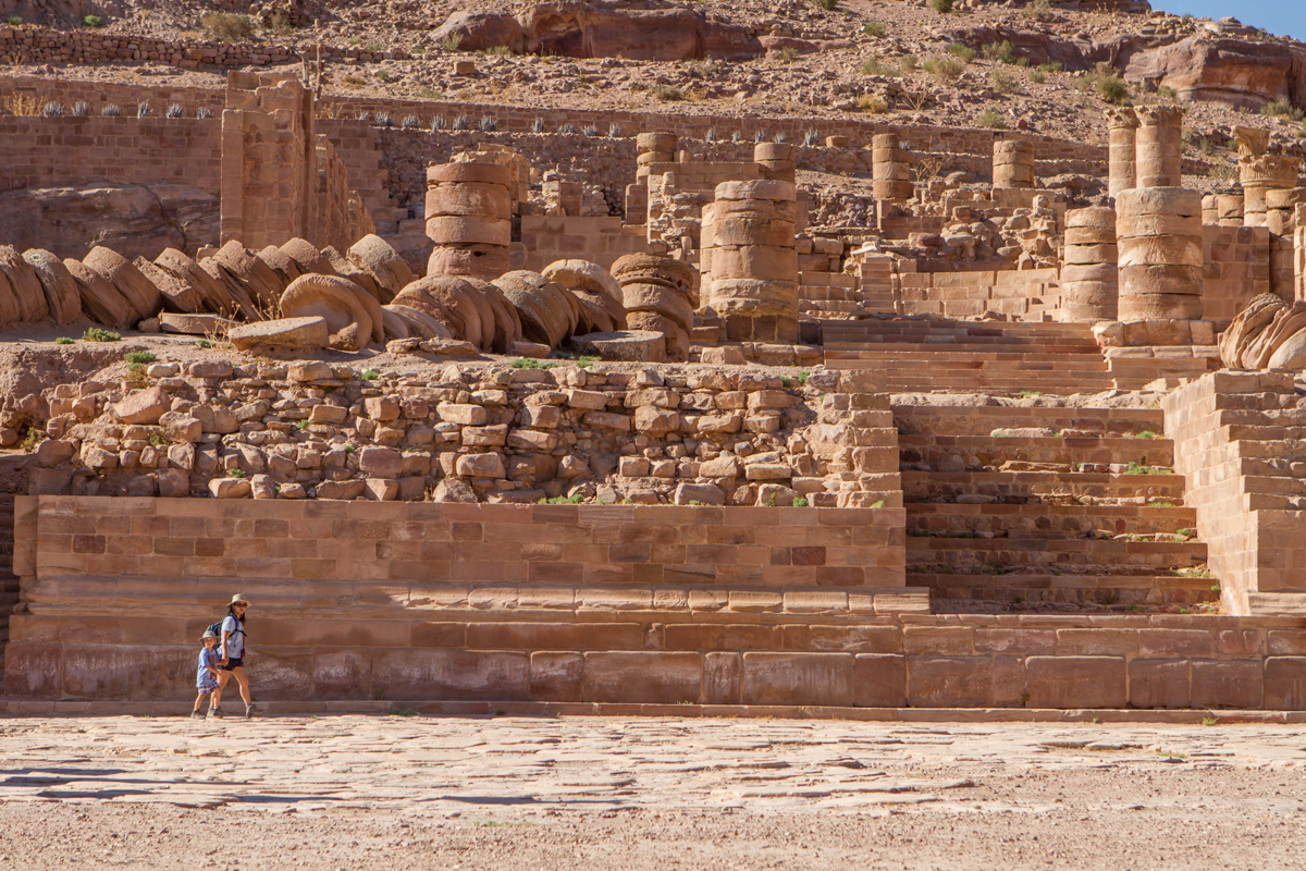 A mother and son walk along the walls of the Great Temple in Petra Jordan