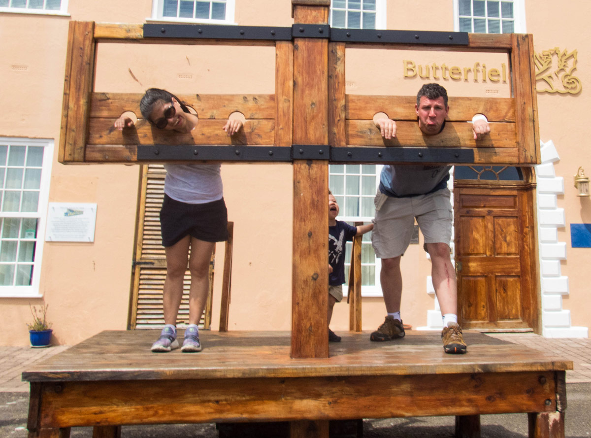 Woman and man pose in a pillory in the town square in St George Bermuda.