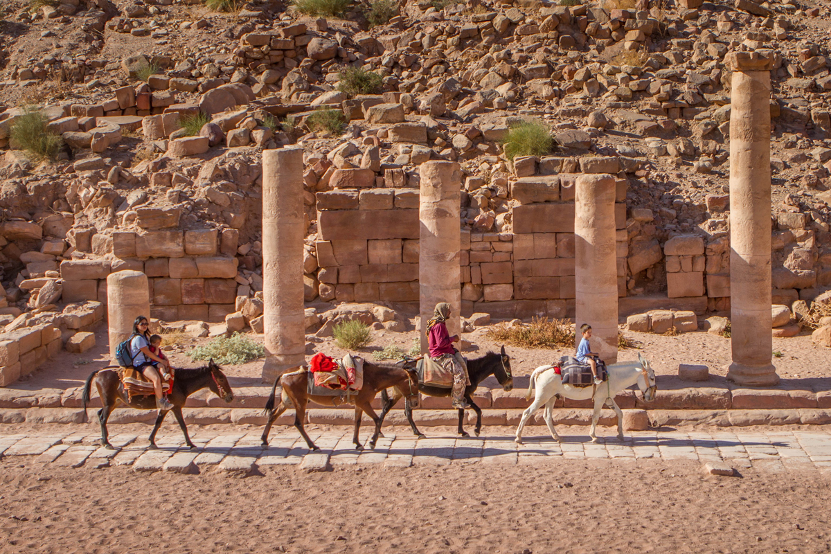 A mother and two sons ride horses along the Colonnaded Street with a Bedouin guide