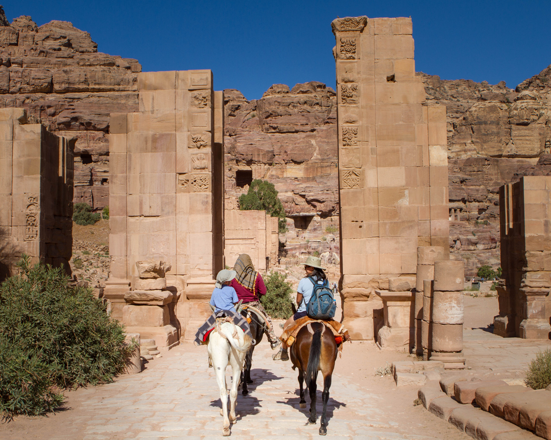Petra for families A Bedouin guides a mother and two young boys on horseback through the Temenos Gateway in on the way to the Monastery