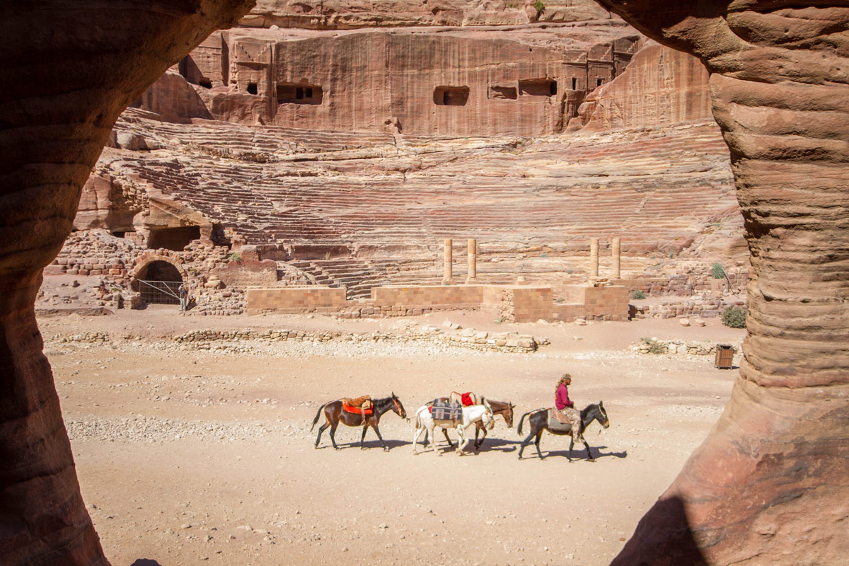 A Bedouin guiding horses strolls in front of the theater as seen from the house across the wadi