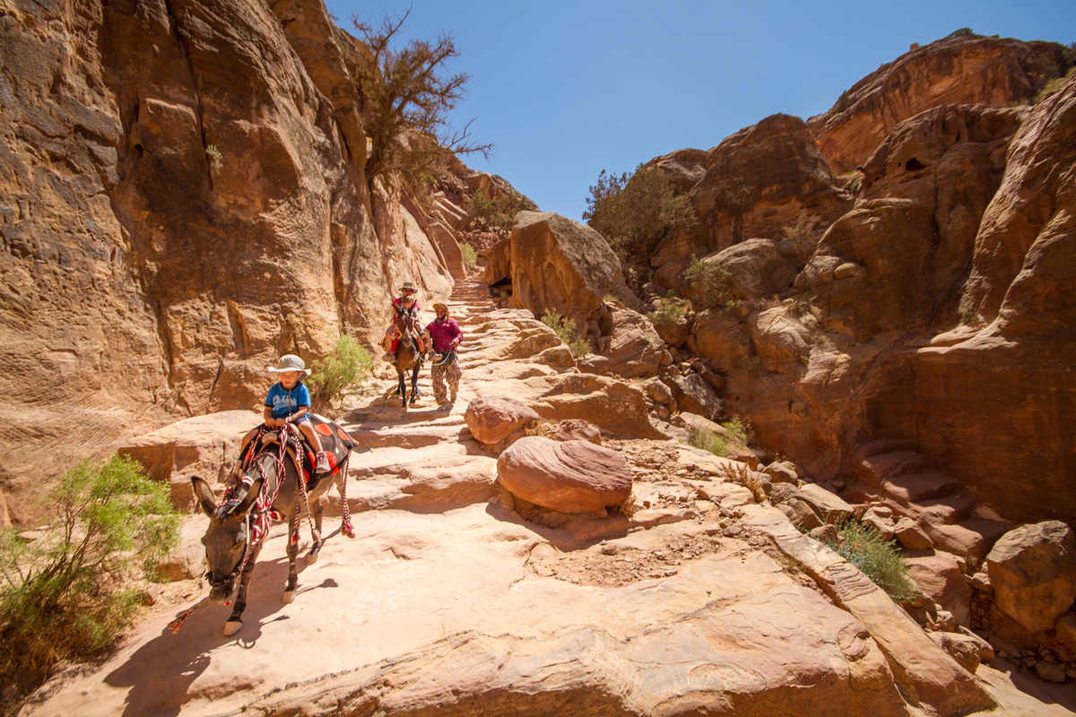A Bedouin guide helps a mother and two boys on horseback make their way down from the high place of sacrifice, the high place is on the list of what to see in Petra with kids