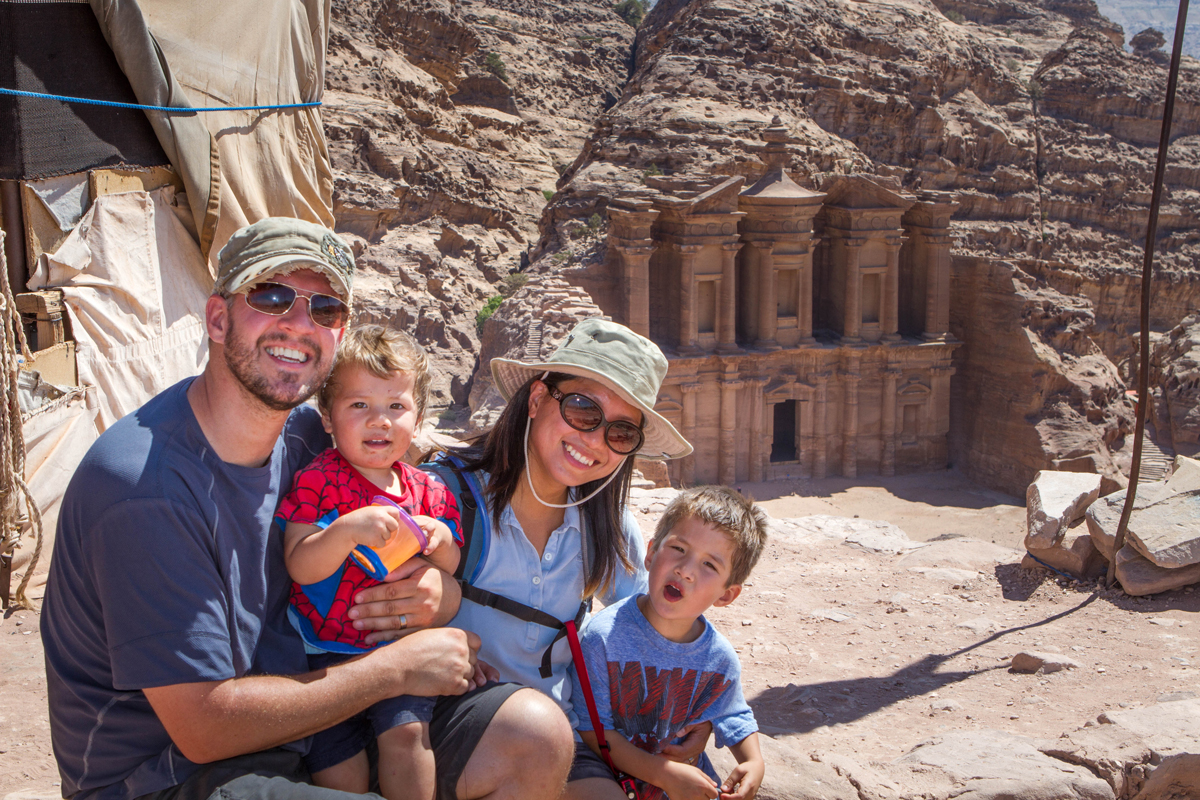 A mixed race family smiles while taking a photo above the Monastery in Petra Jordan. The Monastery is a must if you are looking for what to see in Petra with kids
