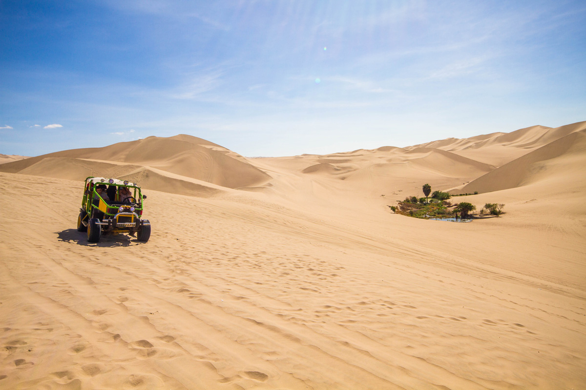 A dune buggy drives through the desert near an oasis as it's occupants prepare to go sandboarding in Peru with kids near Huacachina