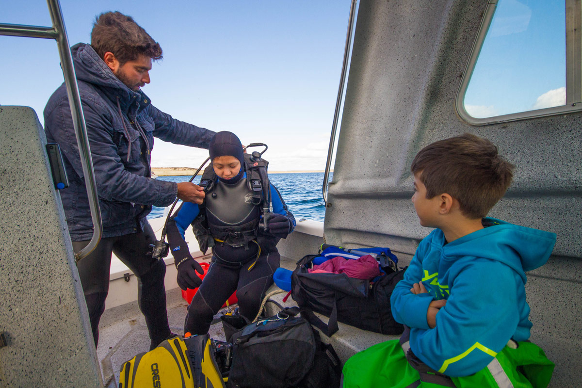 A young boy watches his mother put on SCUBA gear with the help of a dive master as she prepares for Scuba diving with sea lions in Punta Loma