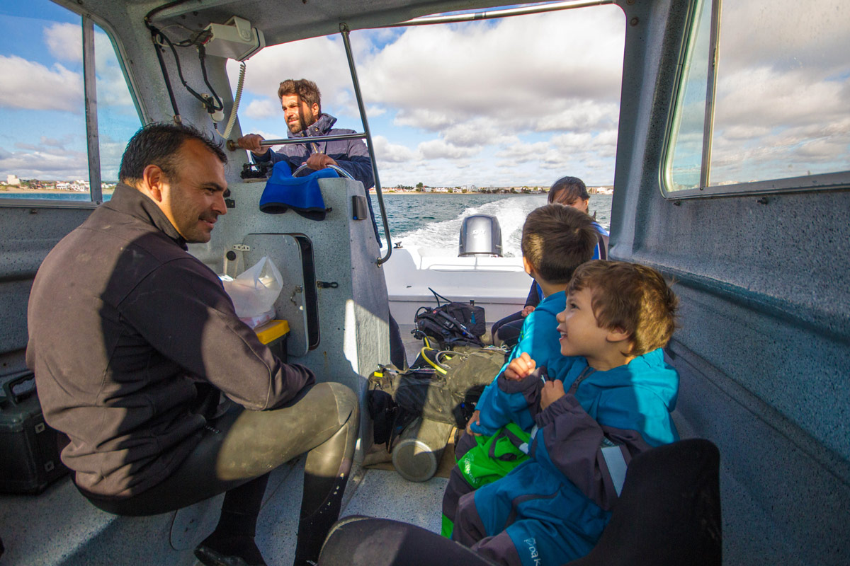 Two young boys chat with a dive master on a small boat in Argentina