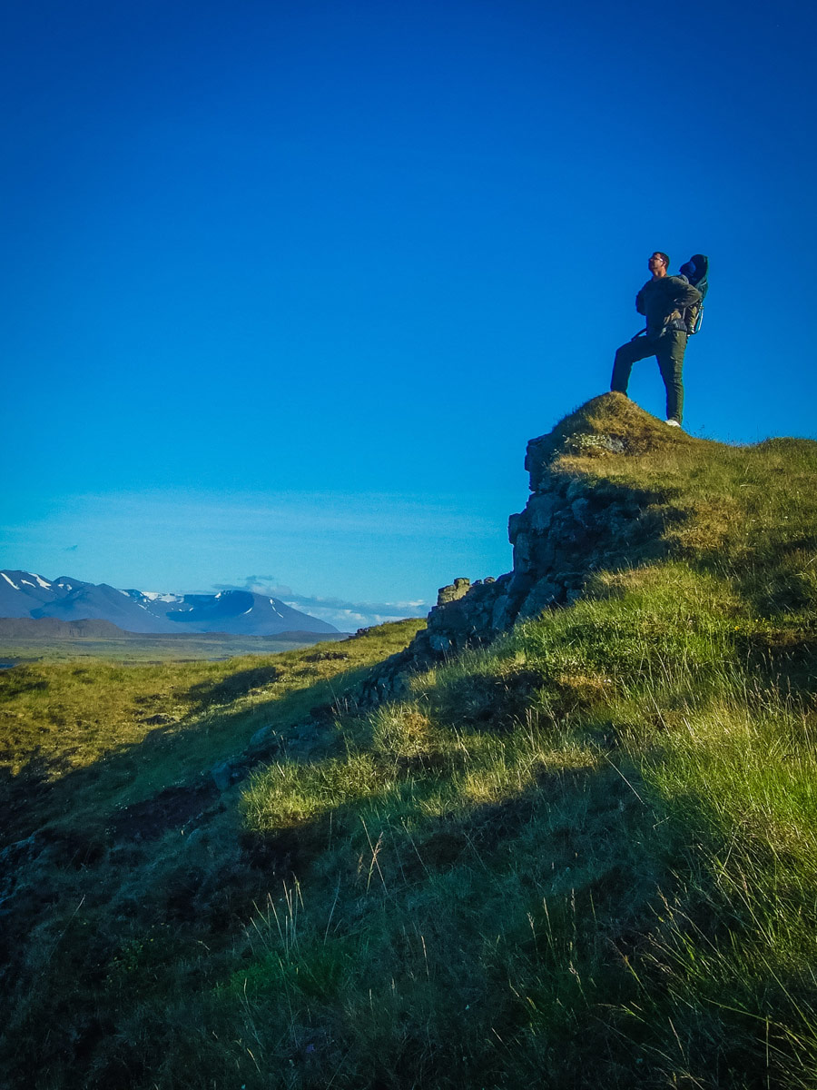 A father hiking with his son in a backpack takes in the view along the Vatnsnes Peninsula in Iceland