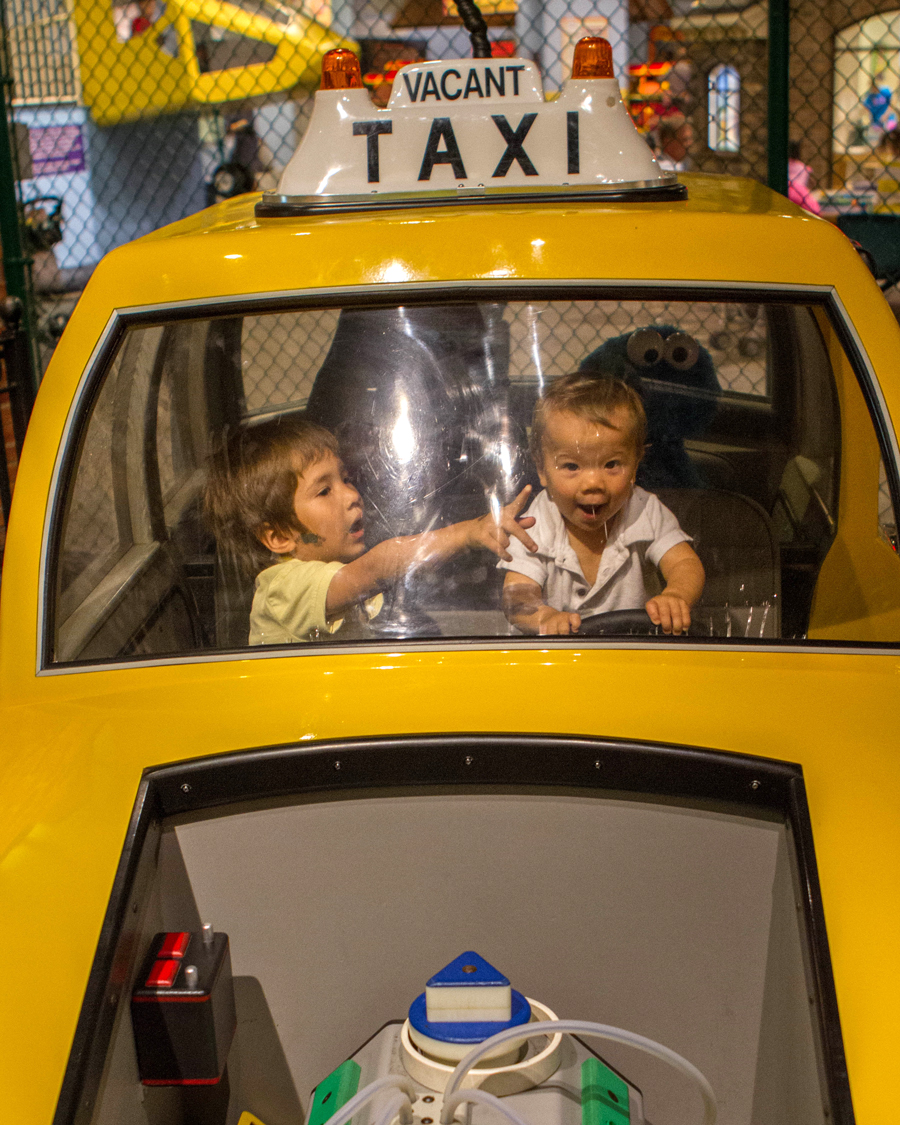 Young toddler takes charge in a taxi at the Museum of Play in Rochester.