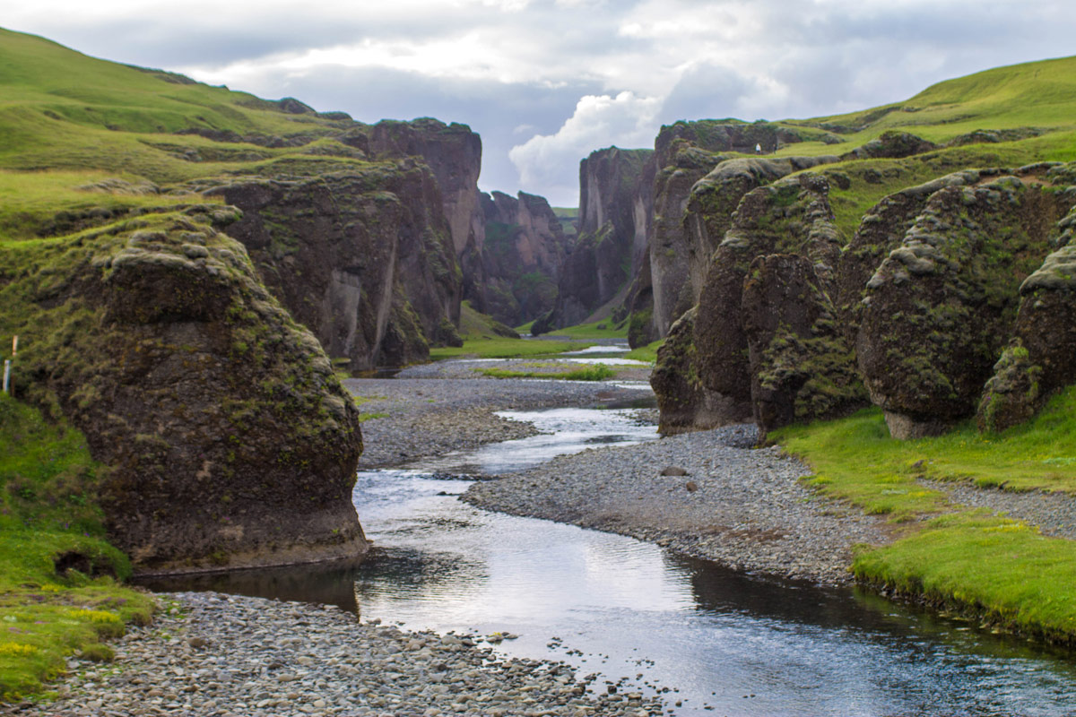 A beautiful misty canyon with a calm river running through it surrounded by tall cliffs topped with green grass