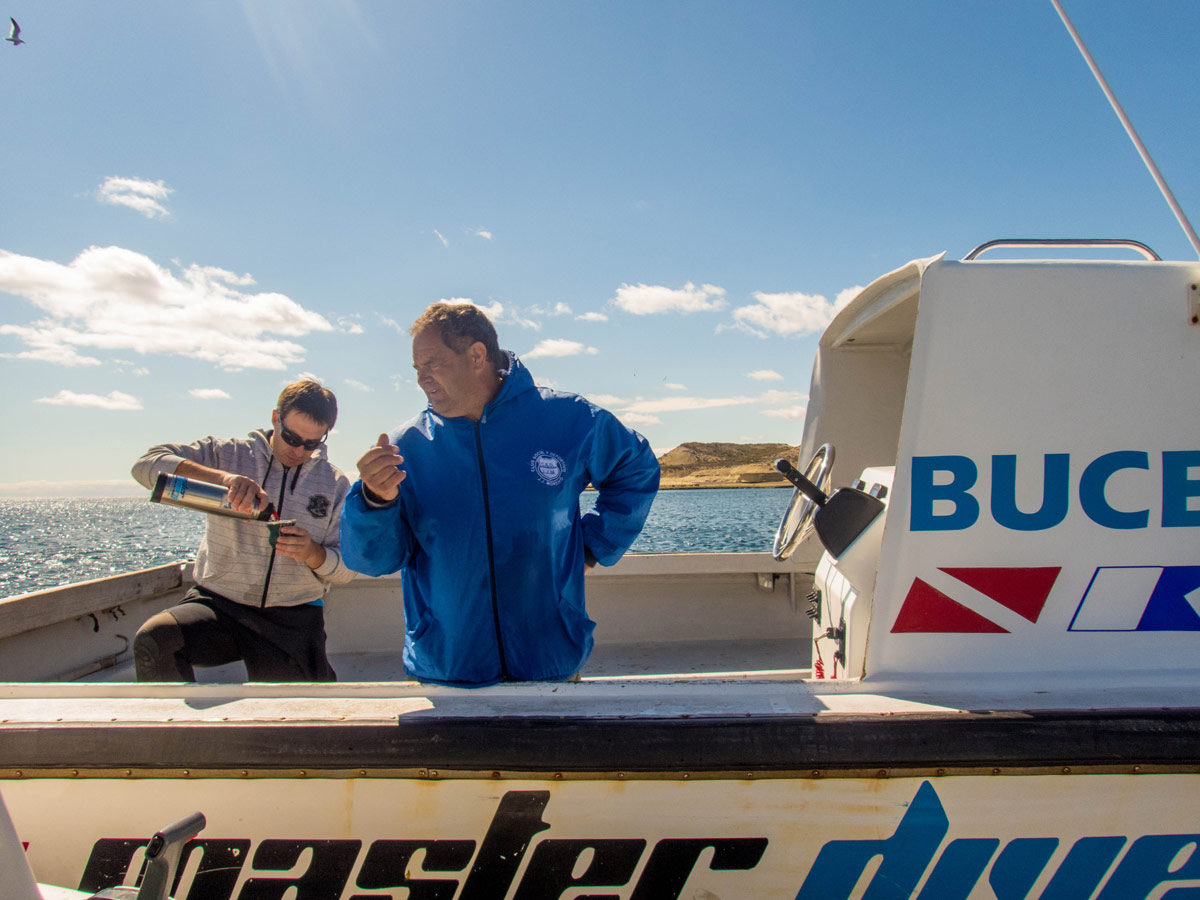 Two SCUBA diving guides drink Mate tea on a dive boat