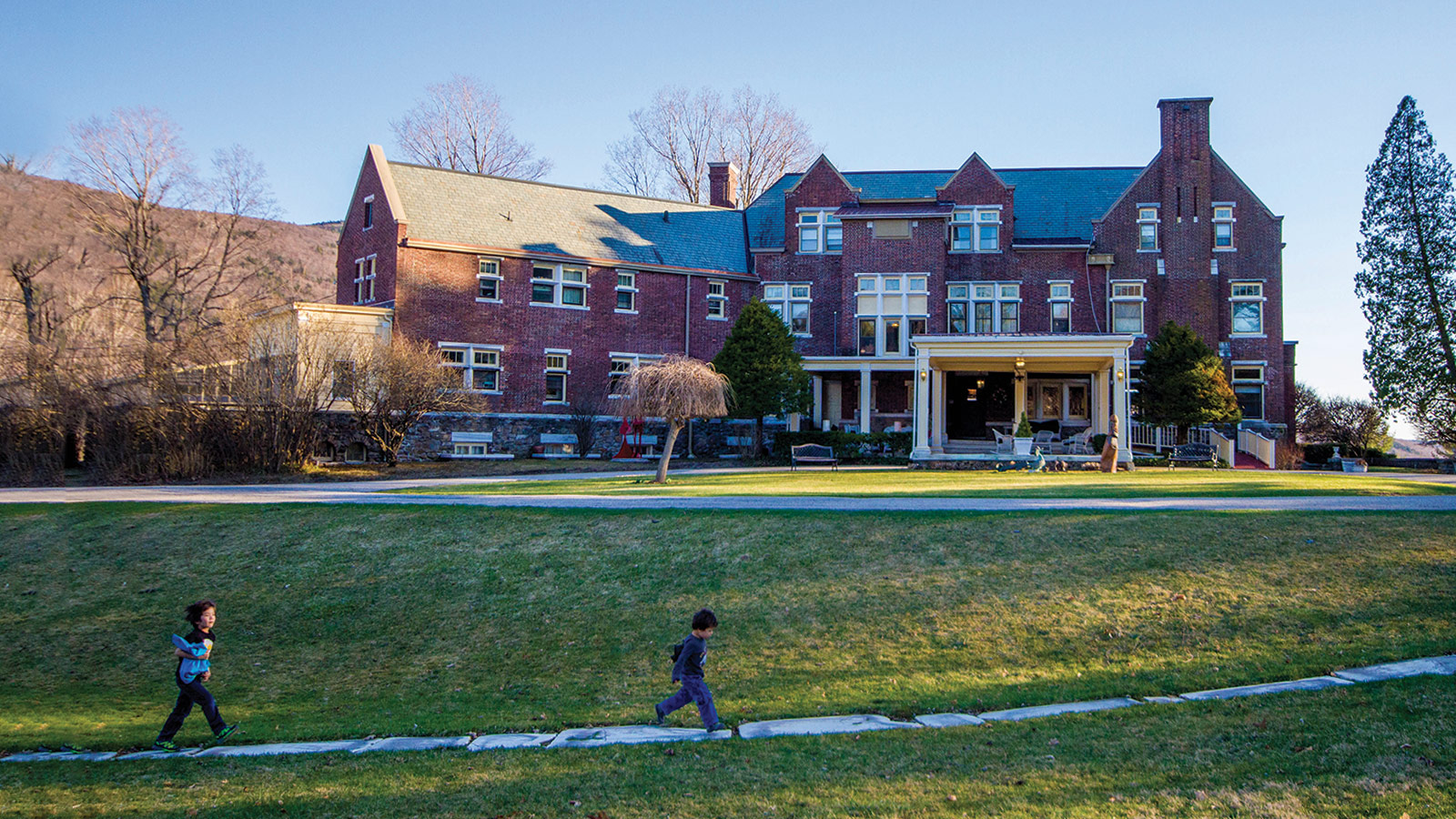 Boy walking on a path in front of The Wilburton Inn which is located on the 30-acre Wilburton Estate in Manchester, Vermont.