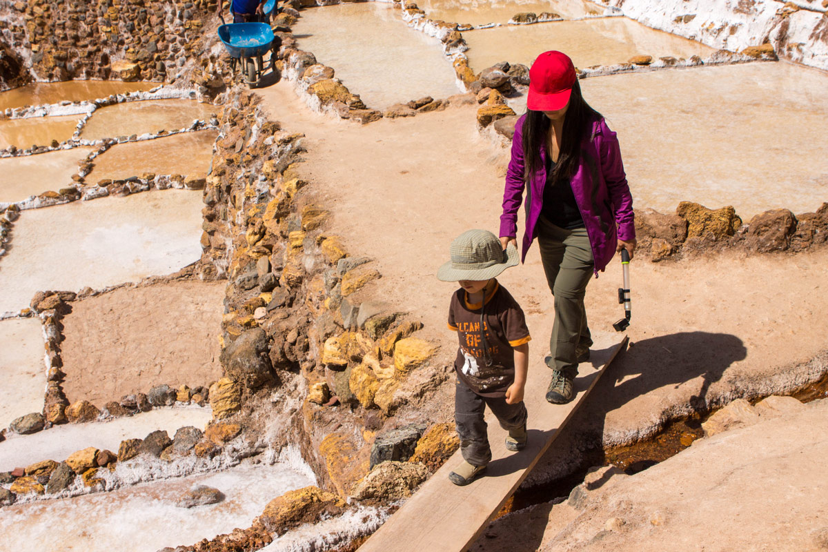 A mother and toddler walk over the boards connecting the salt pans in Maras Peru while visiting Maras and Mora
