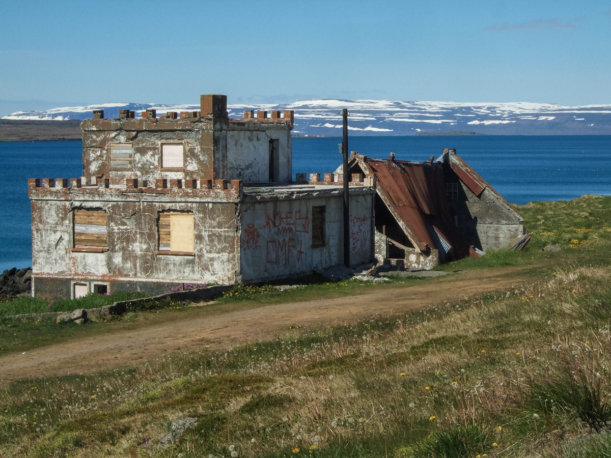 A dilapidated castle-style home on the edge of a fjord in Iceland