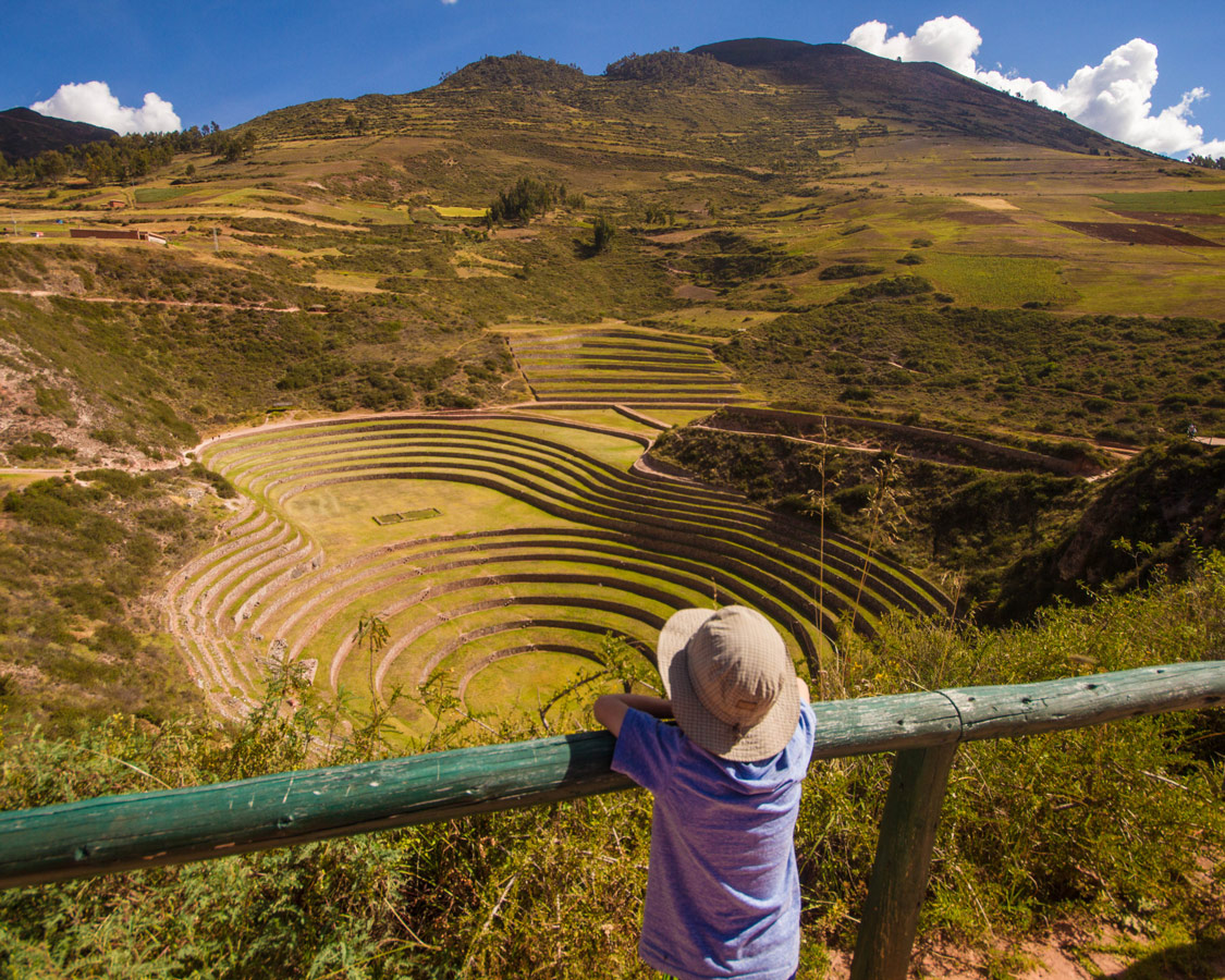 A young boy wearing an explorer hat looking out over the Incan terraces of Moray Peru
