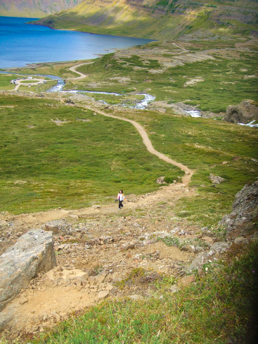 Woman walking along a dirt path among green grass with the ocean in the background