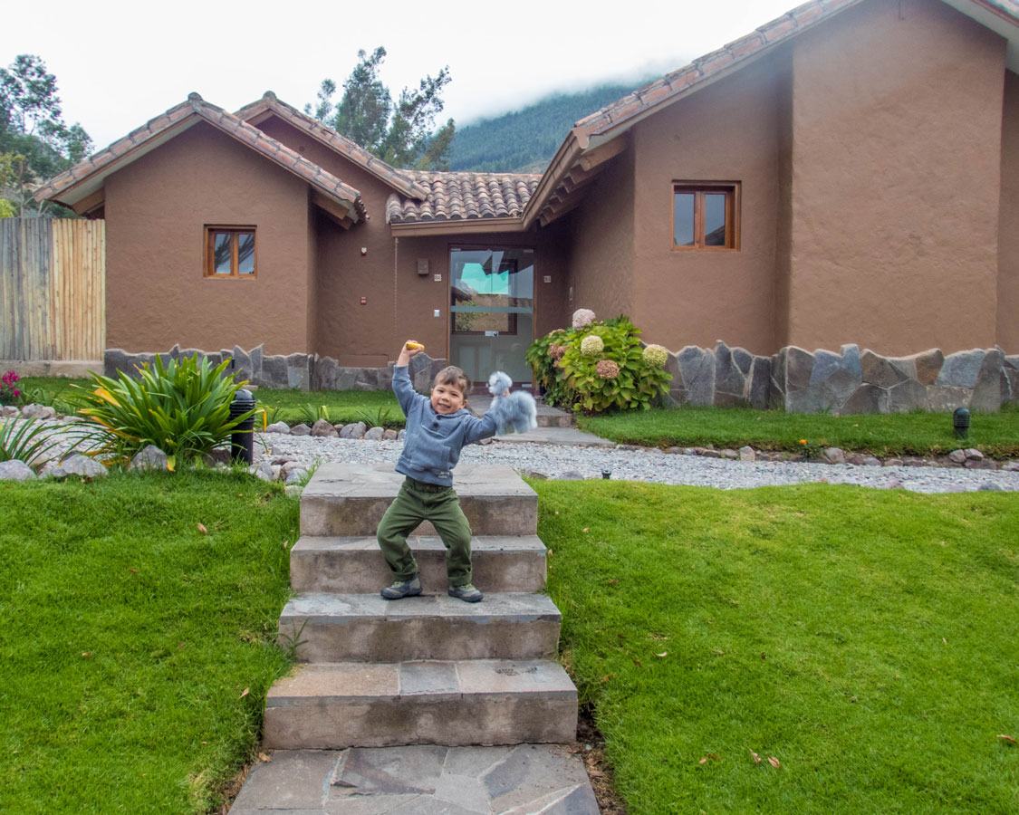 A toddler dances in front of an Andean cottage at the Casa Andina Private Collection Sacred Valley Peru in Urubamba Peru
