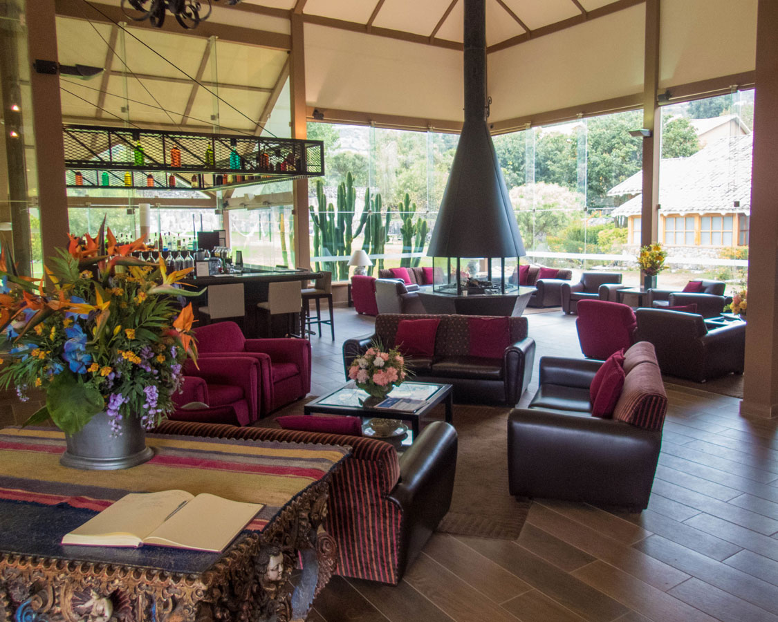 Comfortable chairs, a nice bar and an open fireplace are on display in the main lobby at the Casa Andina Private Collection Sacred Valley Peru