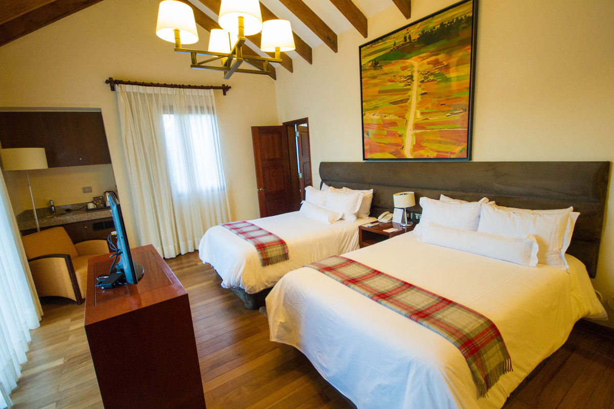 A TV and artwork among the beautiful wood flooring in the Double bed room of the Andean Cottages in Casa Andina Private Collection Sacred Valley Peru