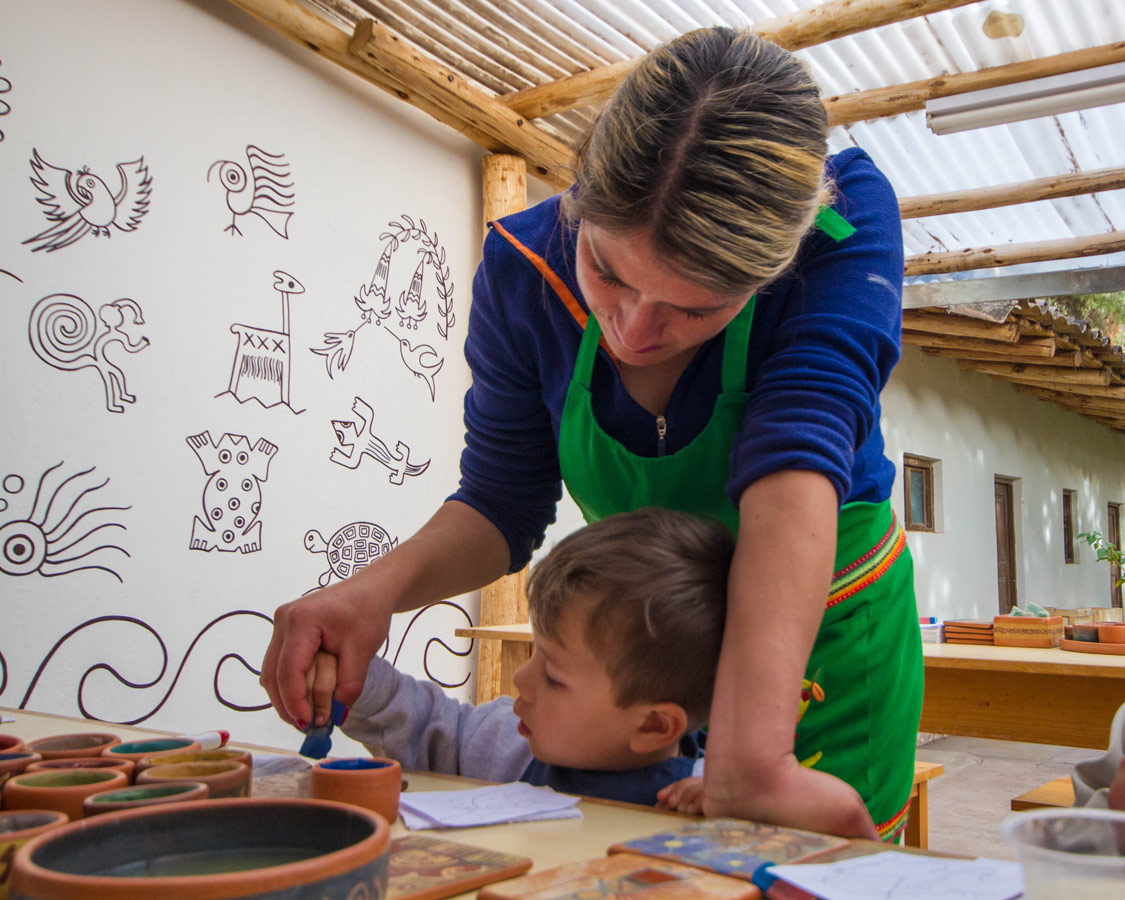 A Ceramic Painting for Kids teacher at Taller Ceramica by Pablo Seminiario helps a toddler work on his pottery painting in Urubamba Peru