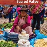 A Quechua woman sells food and grains at the Pisac Market during a day trip to the Sacred Valley Peru