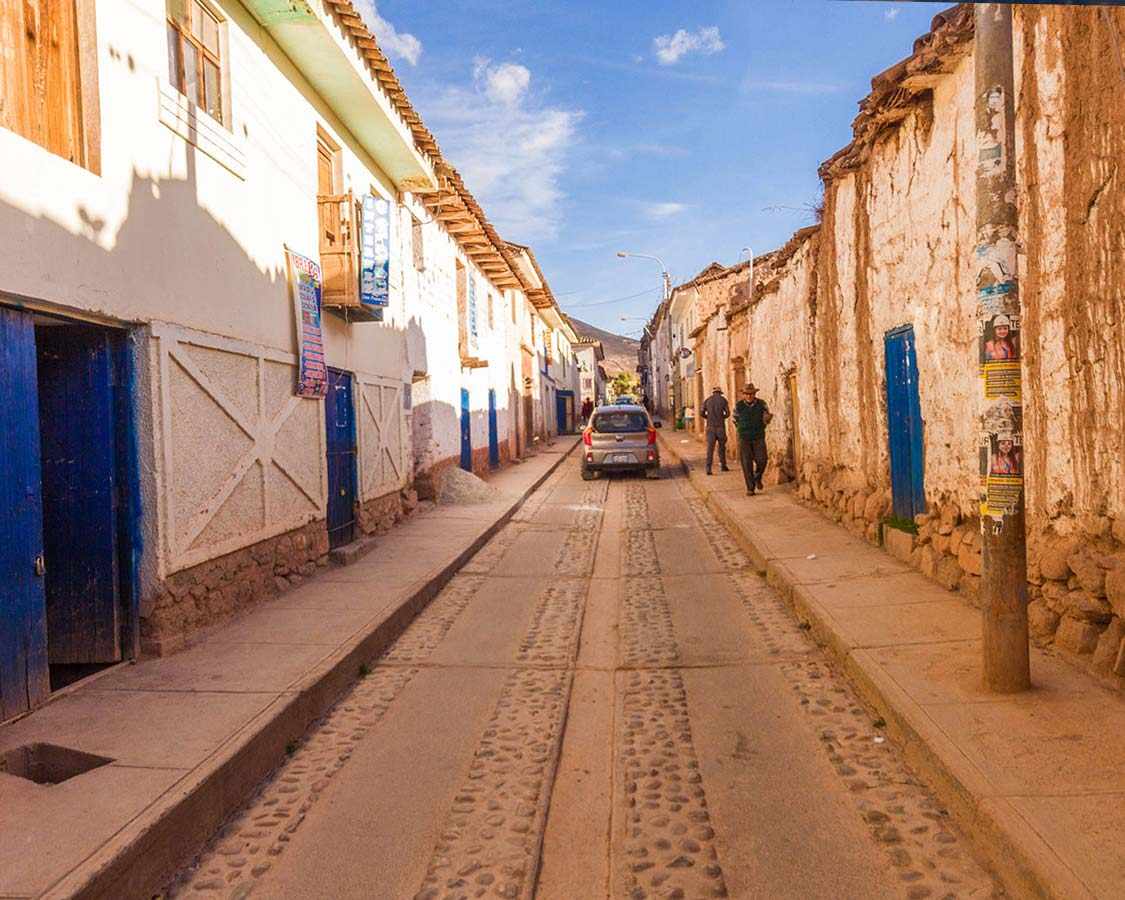 blue doors and adobe buildings in a beautiful street seen in Moray Peru on a day trip to the Sacred Valley Peru