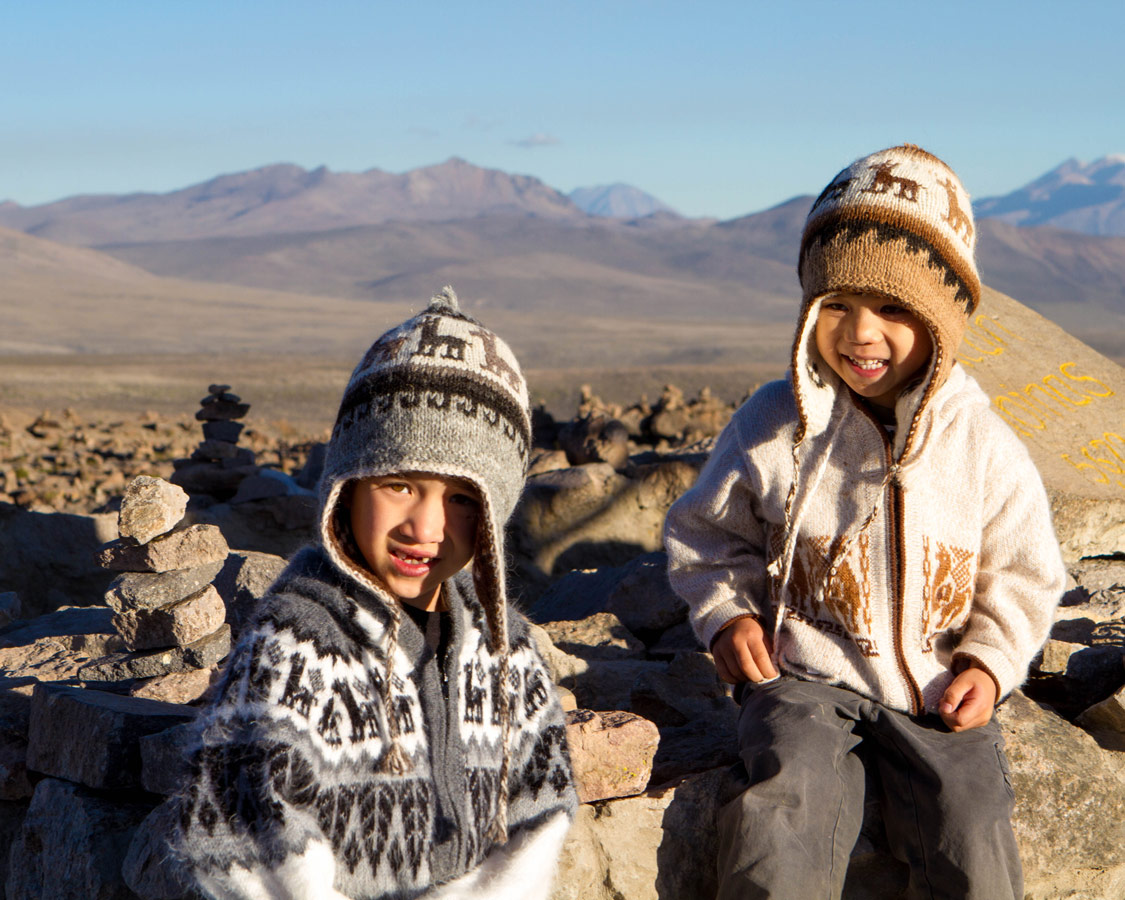 Two young boys wear alpaca hats and sweaters smile among piled rocks at Patapampa Pass in the Andean Mountains on the way to see the Andean Condors in Colca Canyon with kids