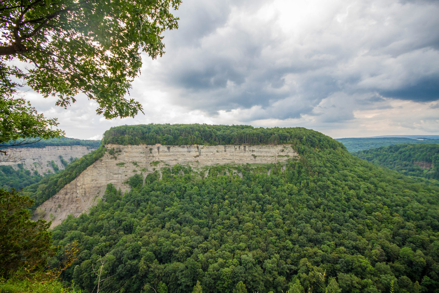 A gorge wall topped with trees above a calm river at Big Bend in Letchworth State Park in New York State