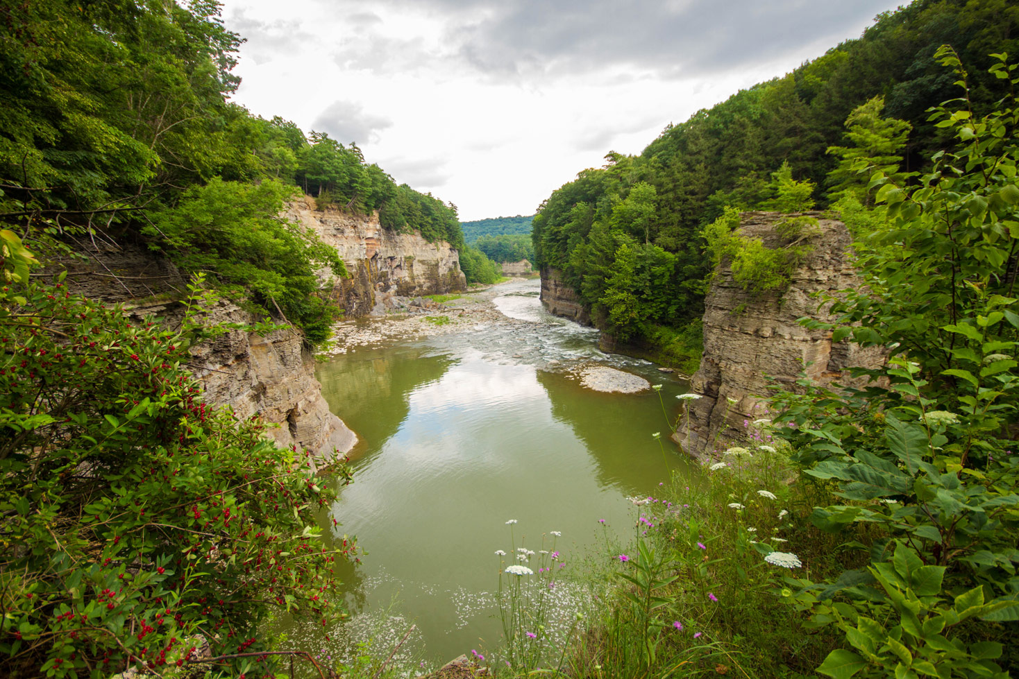 The walls of the gorge tower over the Letchworth River in Letchworth State Park with kids in New York State