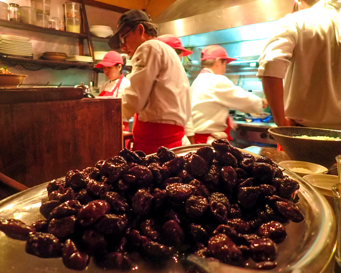 A plate of dates sits in front of the busy kitchen at Cicciolina restaurant, one of the best places to eat in Cusco Peru