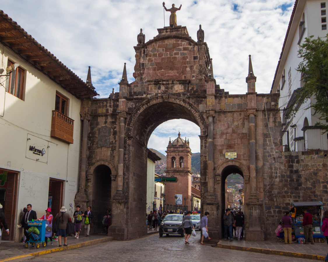 Crowds pass through the Arco Santa Clara , a stone arch across the road. This is one of the top things to do in Cusco