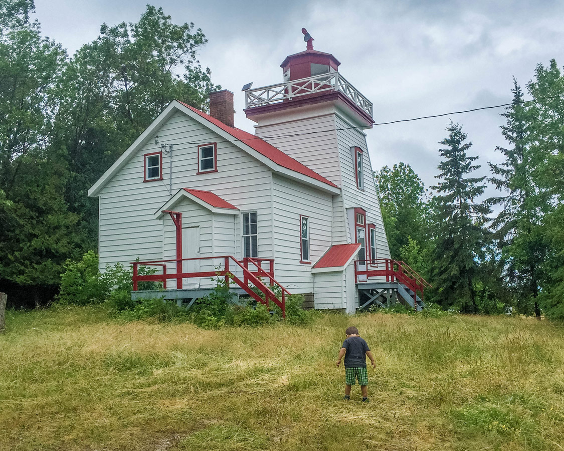A young boy explores the grounds of the Janet Head Lighthouse on Manitoulin Island. It's one of the best things to do on Manitoulin Island