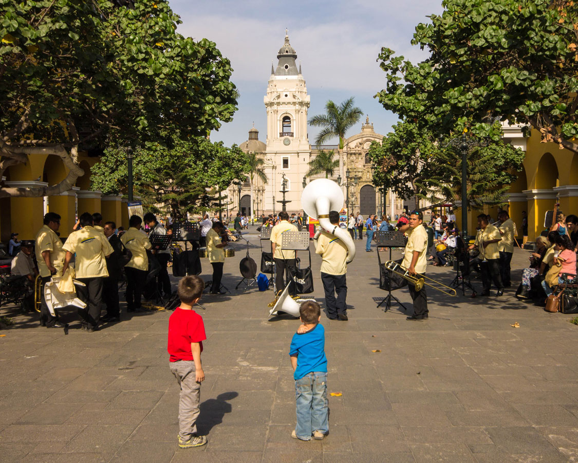 Boys watching a band play on the streets of Lima Peru with kids during 2 weeks in Peru