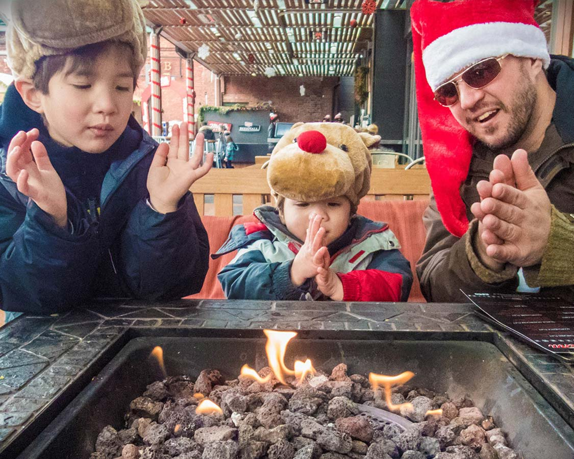 A man wearing a Santa hat and two young boys wearing rudolph hats warm themselves by a fire at a Christmas Market