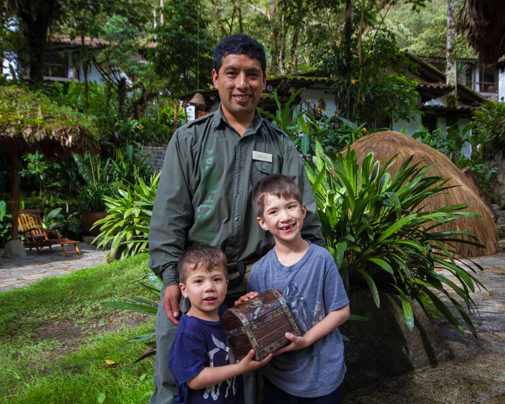Two young boys stand with a guide while holding a treasure chest at the InkaTerra Machu Picchu Pueblo Hotel in Peru