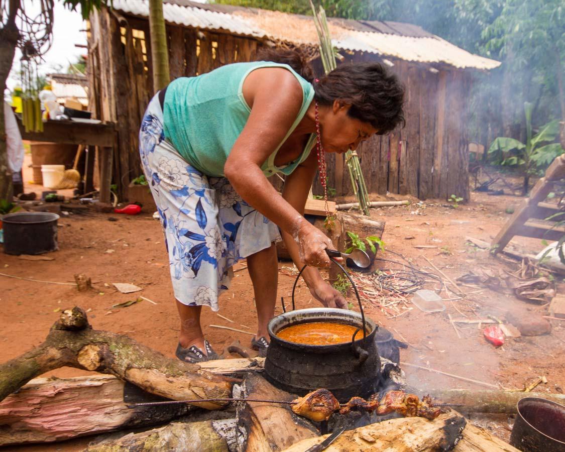 A Guarani tribeswoman makes a stew outside a hut near San Ignacio Argentina