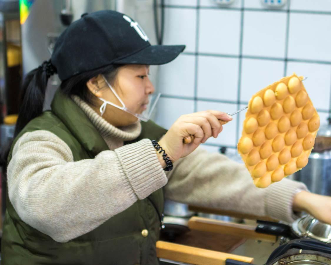 A shopkeeper at Law Kong Yuen Milk Tea Shop makes Shanghai-style waffles on a food tour