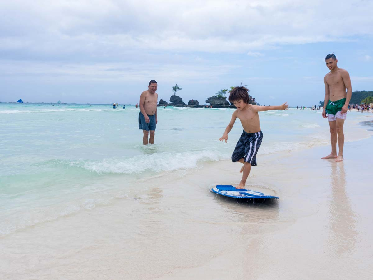 Adults cheer on a young boy skimboarding in Boracay Philippines