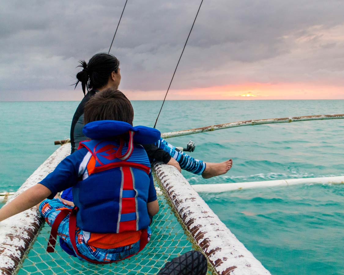 Mother and son enjoying a Paraw Sailing sunset cruise in Boracay Philippines
