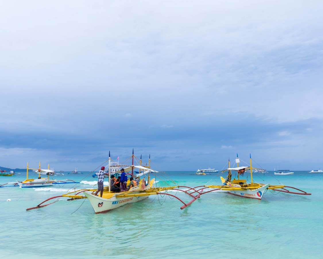 Paraw boats docked in the blue water at Station 2 in Boracay Philippines