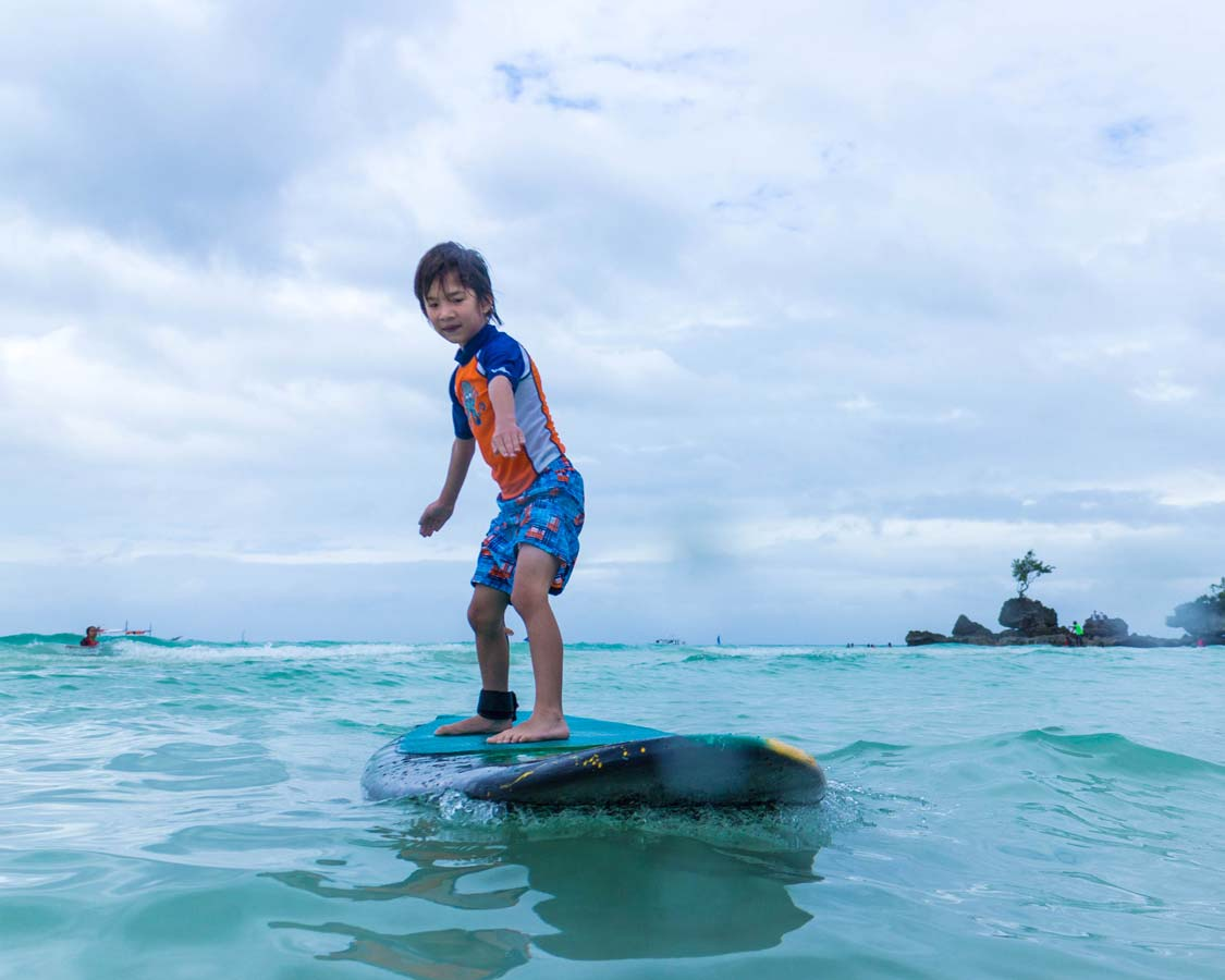 Young boy surfing in Boracay Philippines