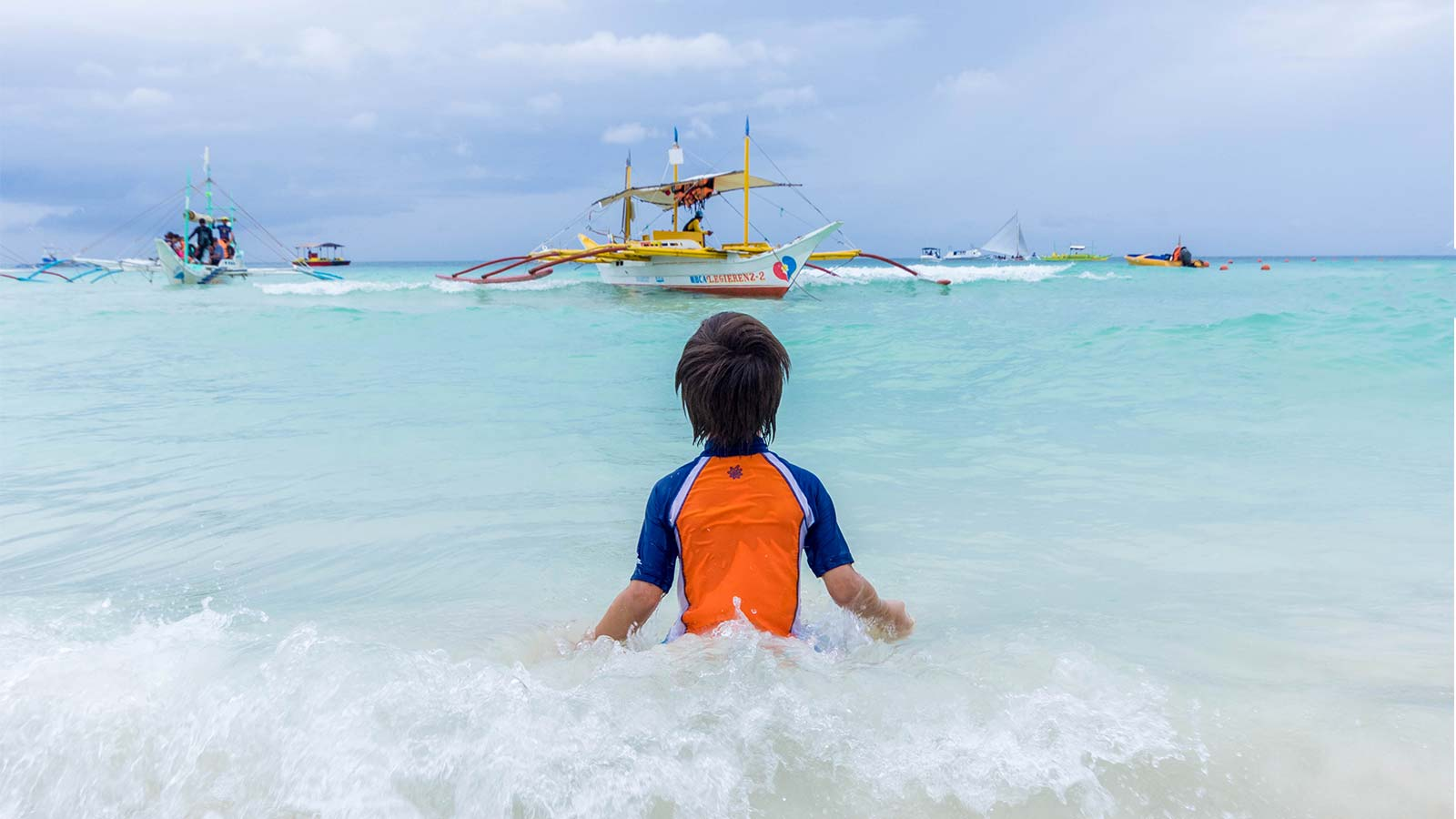 A young boy plays in the surf on Boracay Beach