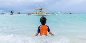 A boy plays in the ocean while Paraw boats float in the distance