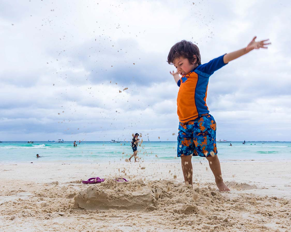 A young boy breaks a sand castle on Whites Beach in Borcay with kids