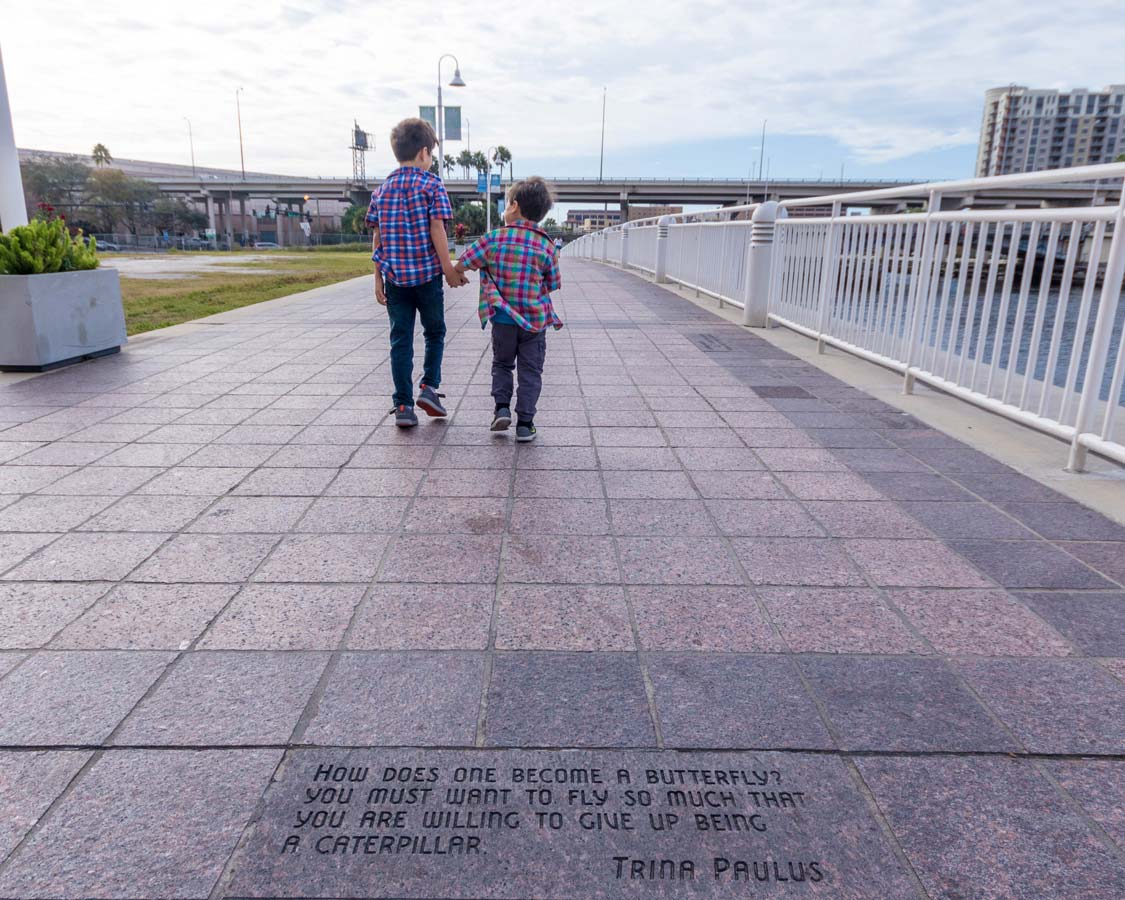 Two boys walk along the Tampa Riverwalk in Florida
