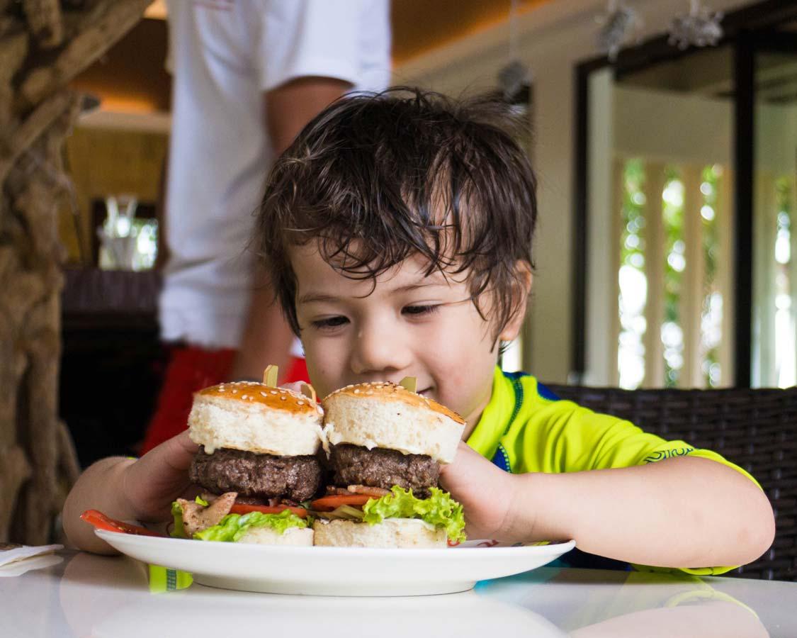 boy eating a big hamburger at the Movenpick Boracay hotel