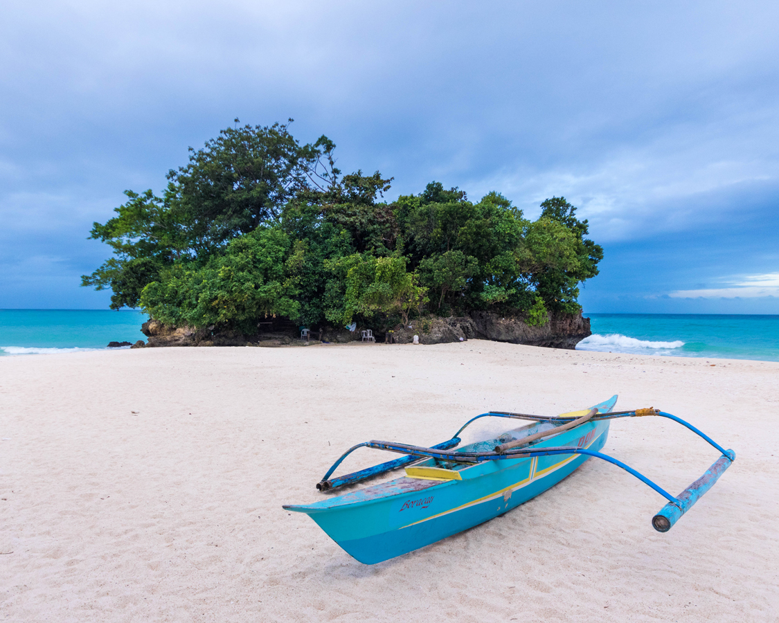 Paraw boat on the beach in front of a small island in Boracay Philippines