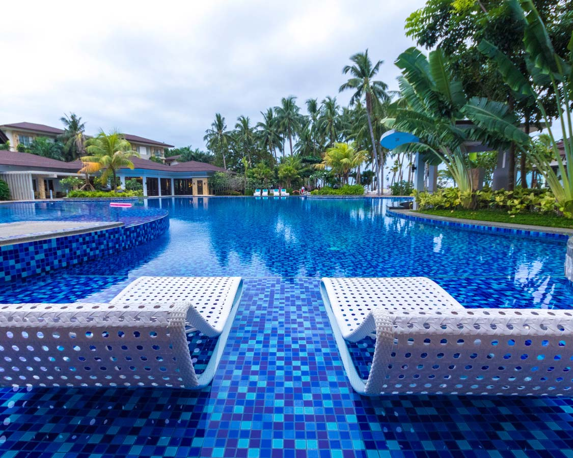 lounge chairs by the pool at the Movenpick Boracay hotel