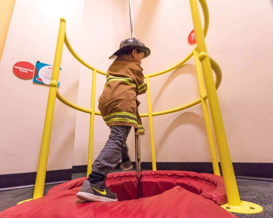 A young boy in a firefighter outfit slides down a pole at the Glazer Children's Museum in Tampa Florida